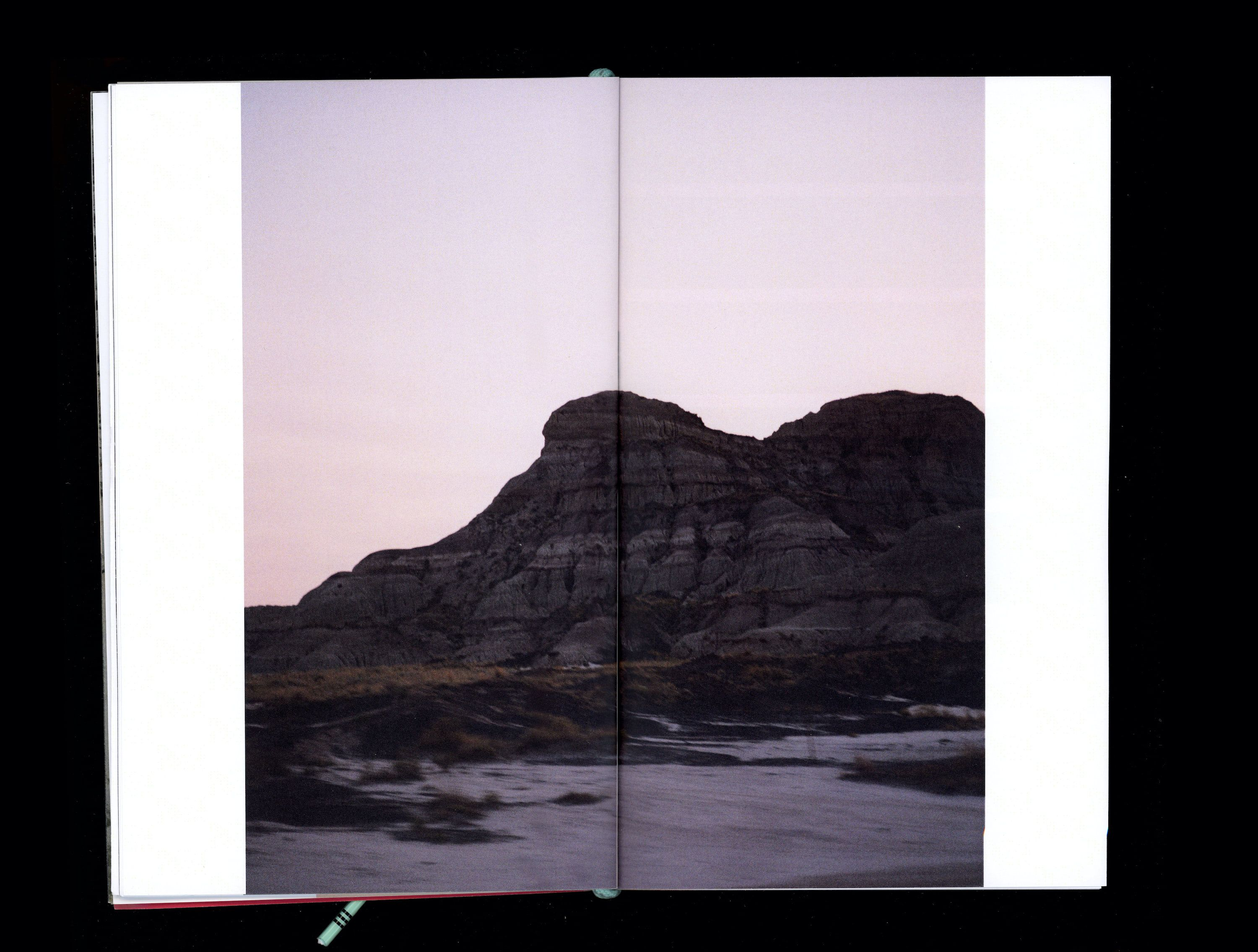 Photograph in book of rock with striations in front of pink sunset