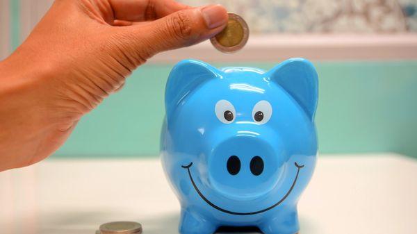 Someone putting money in a piggybank
