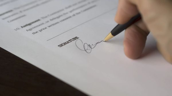 A hand signing financial paperwork