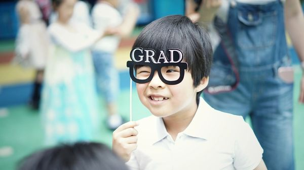 A child wearing grad cap