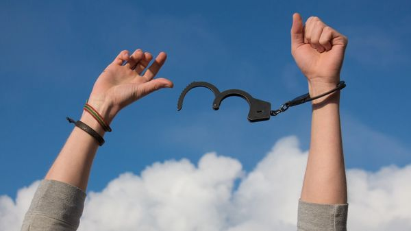 Image of hand unshackled by handcuffs
