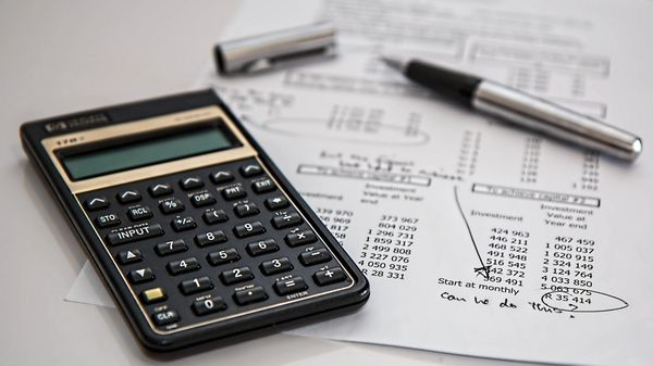 A calculator beside a pen and some fniancial statements