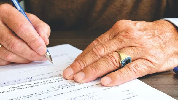 A wrinkled hand filling out paperwork