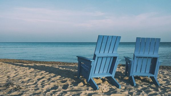 Two chairs on a beach.