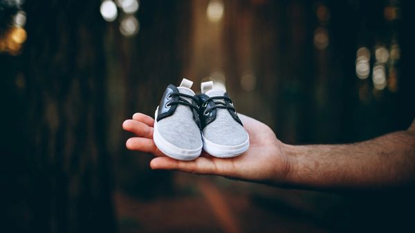 a hand holding a pair of baby shoes