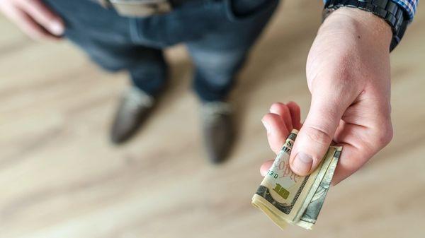 A man holding a ten-dollar bill