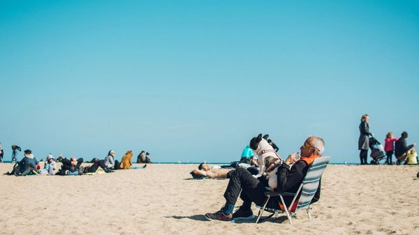 A retired couple sitting on lawn chairs on the beach