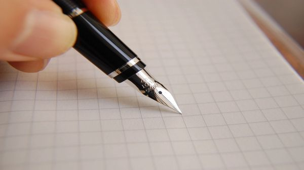 Pen writing on graph paper.