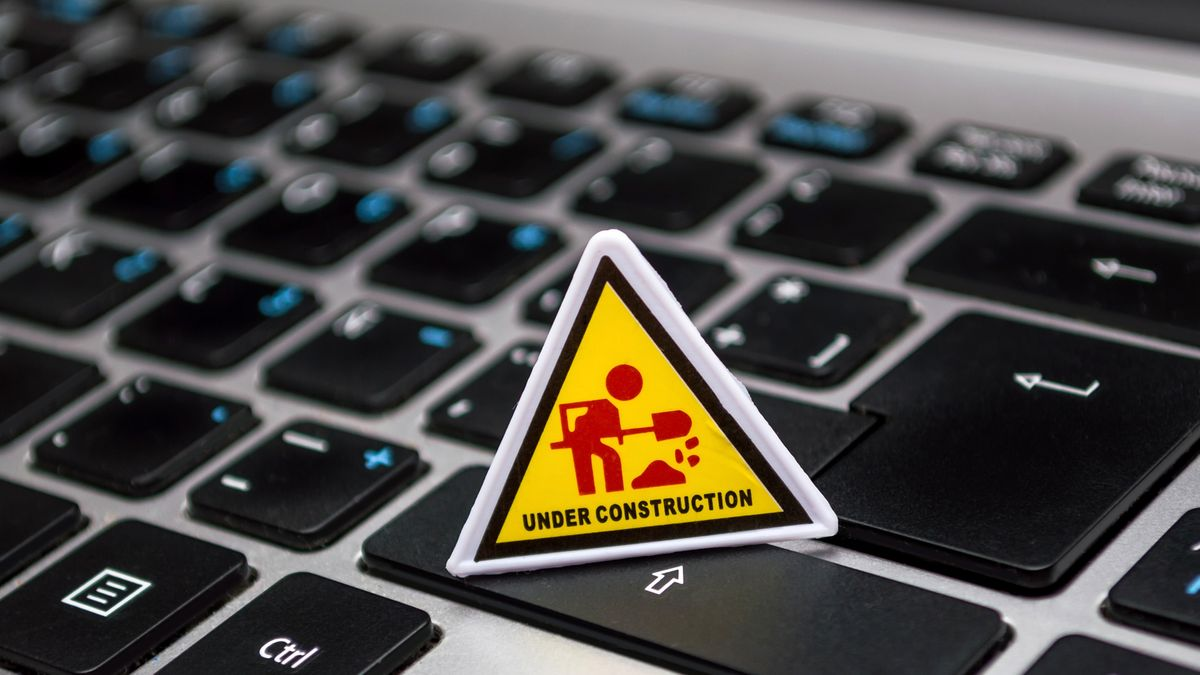 """A computer keyboard with an """"under construction"""" sign on it."""