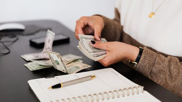 An image of a payroll clerk counting money