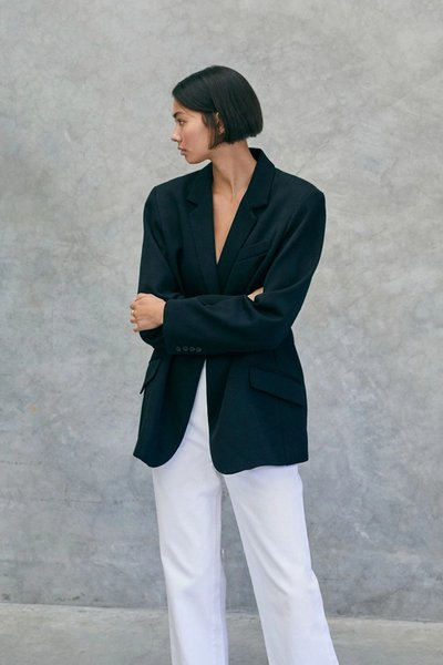 Model wearing the 01 Blazer Black with the 01 Jeans in Ivory.