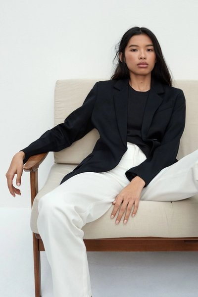 Model sitting down, wearing the 01 Blazer Black with the 01 Jeans in Ivory.