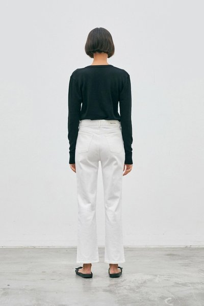 Back shot of model wearing the 01 Cardigan Black with the 01 Jeans Ivory.