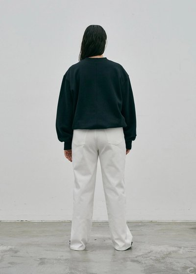 Model wearing the Crew Neck Sweatshirt Black with the 01 Jeans Ivory. Turned around to show the back.