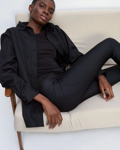 Model sitting down wearing the 01 Legging Black with the 01 Shirt Black.