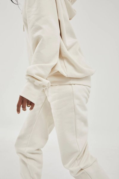 Close up of model wearing the Track Pants Bone with the 01 Hoodie Bone.