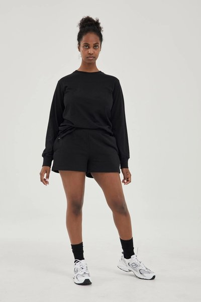 Model wearing the Track Shorts Black with the Long Sleeved T-shirt Black.