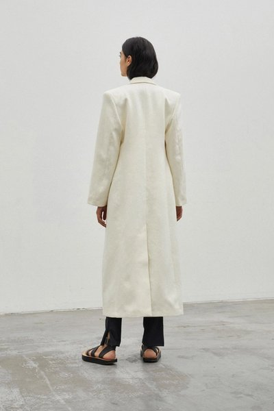 Back shot of model wearing the Sprinkling of Strength Coat Ivory with the 01 Leggings Ivory.