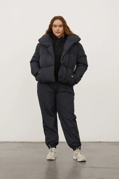 Model wearing the Spray Track Pants with the Beyond Puffer in black.