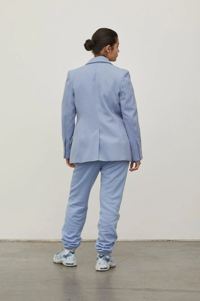 Model wearing the Track Pants in Powder Blue with the 01 Blazer. Turned around to show the back.
