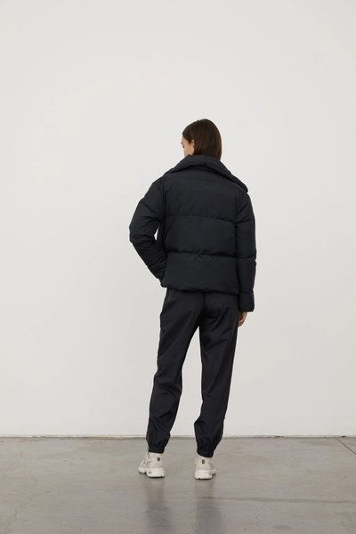 Back shot of model wearing the Beyond Puffer Black with the Spray Track Pant Black.