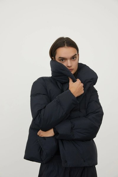Close up of model wearing the Beyond Puffer Black with the Spray Track Pant Black.