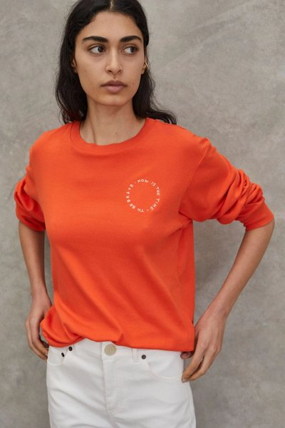 Model wearing the Now is the Time to be Brave Top Orange.