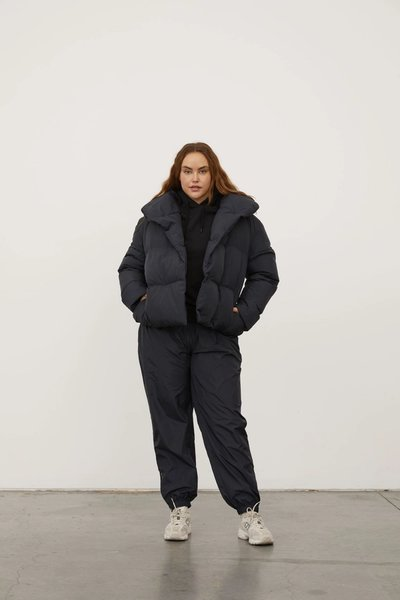 Model wearing the Beyond Puffer Black with the Spray Track Pant Black.