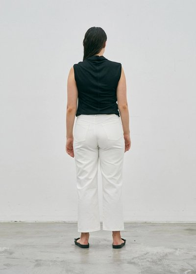 Model wearing the 01 Turtleneck Singlet in black with the 01 Jeans in Ivory, turned around to show the back.