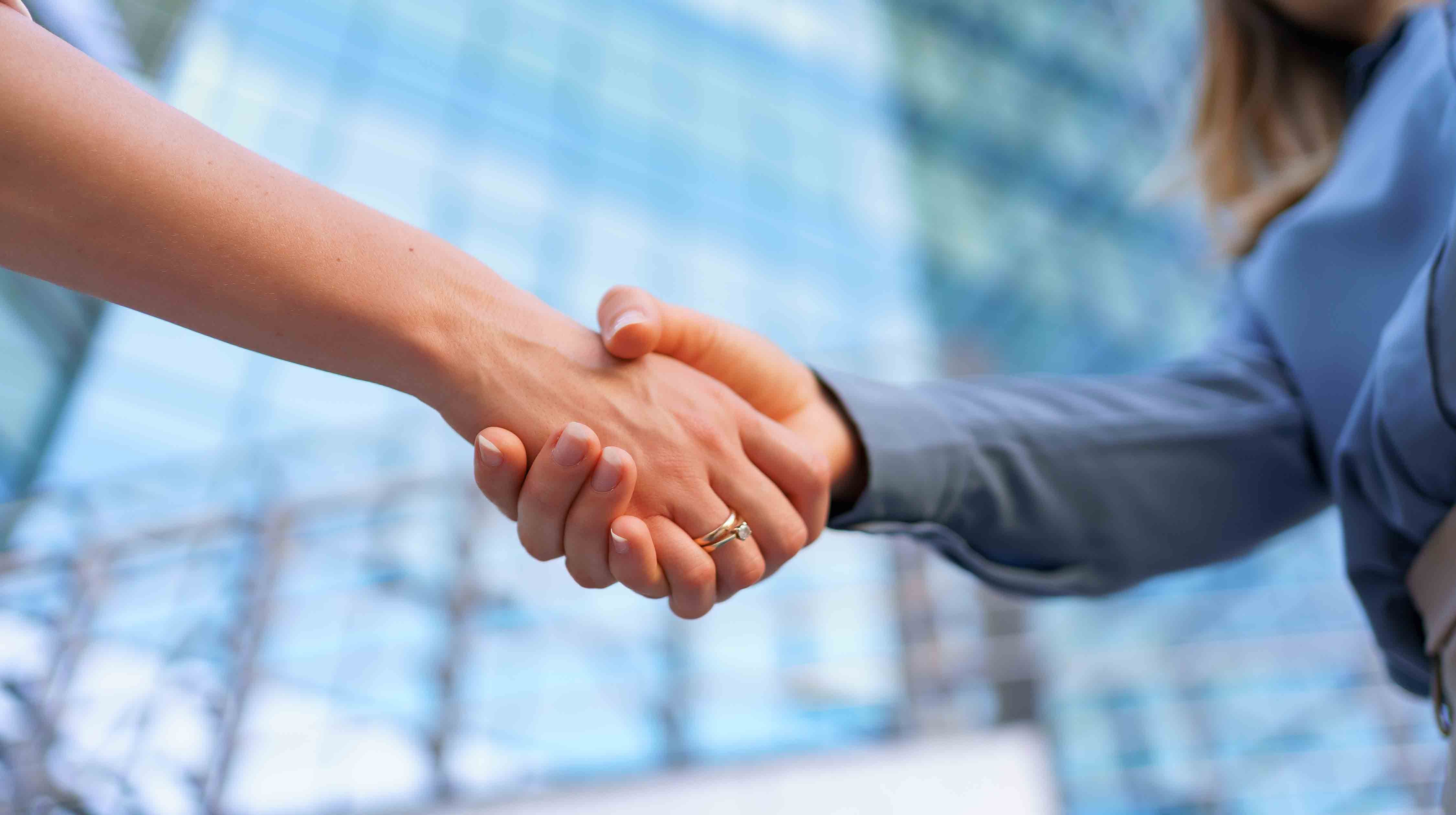 woman-handshaking-outdoors-modern-glass-business-building-close-up-picture-1.jpg