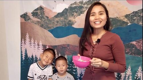 a mother treats her two young boys to some sweets in a bowl