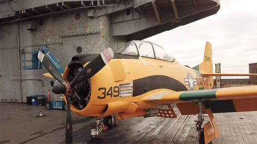 on the deck of an aircraft carrier, viewing a World War 2 aircraft bright yellow