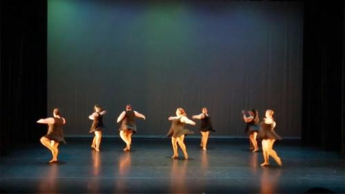 seven ladies in black dresses dancing on a large stage with black curtains
