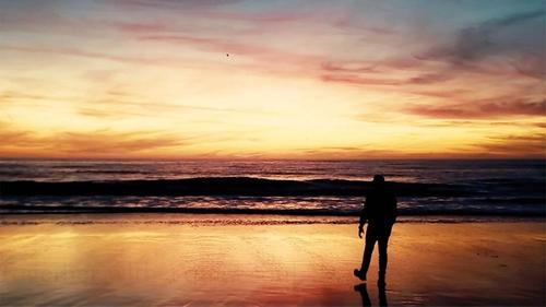man alone on a quiet beach at glorious sunset