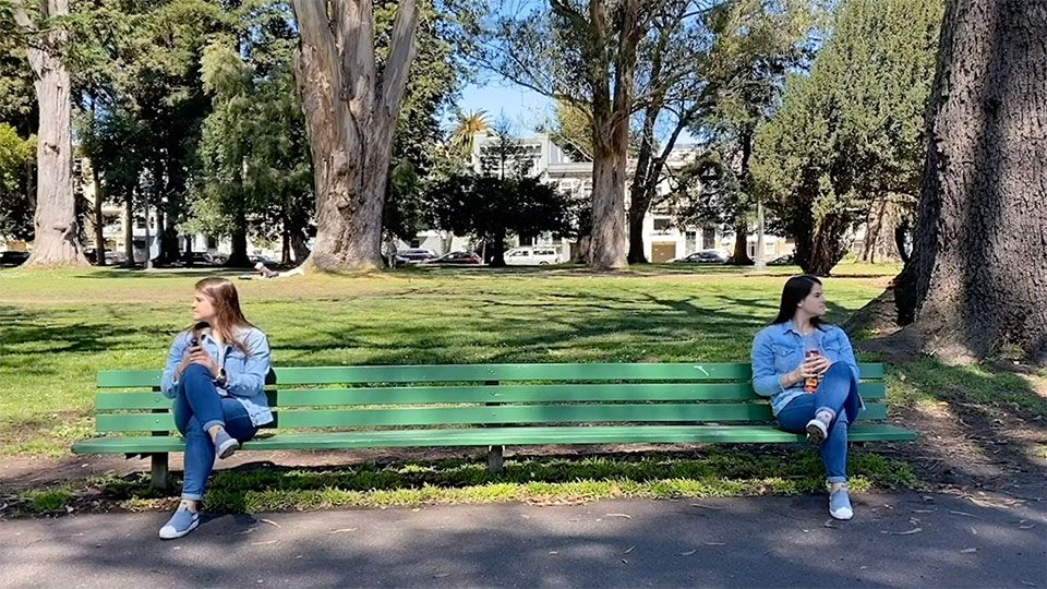two young women sit on opposite ends of a long bench, ignoring each other