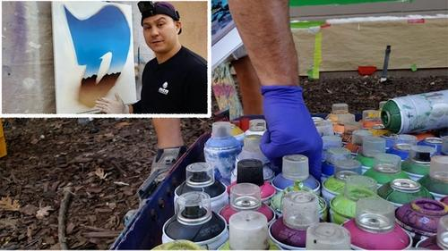 Young man demonstrating wall art using hundreds of different paint cans