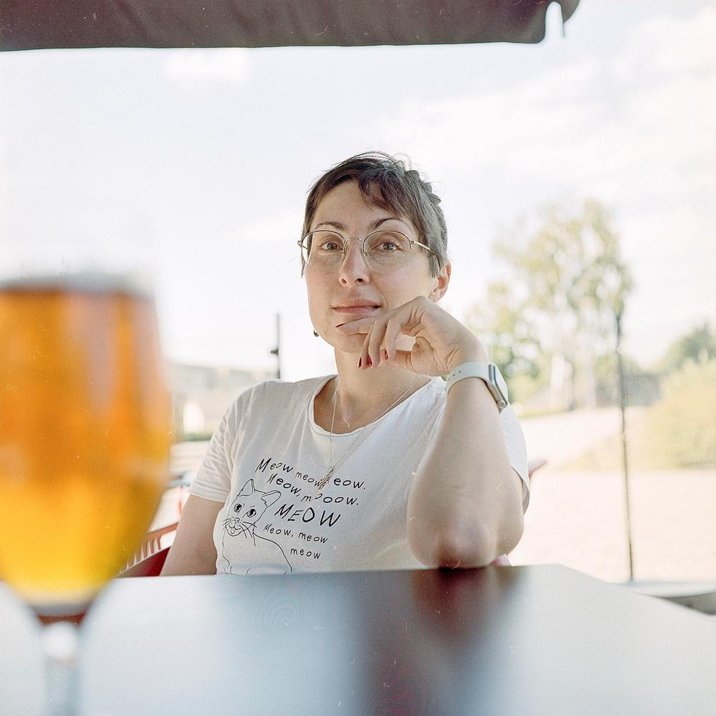 Photo of my wife with blurred beer in foreground.