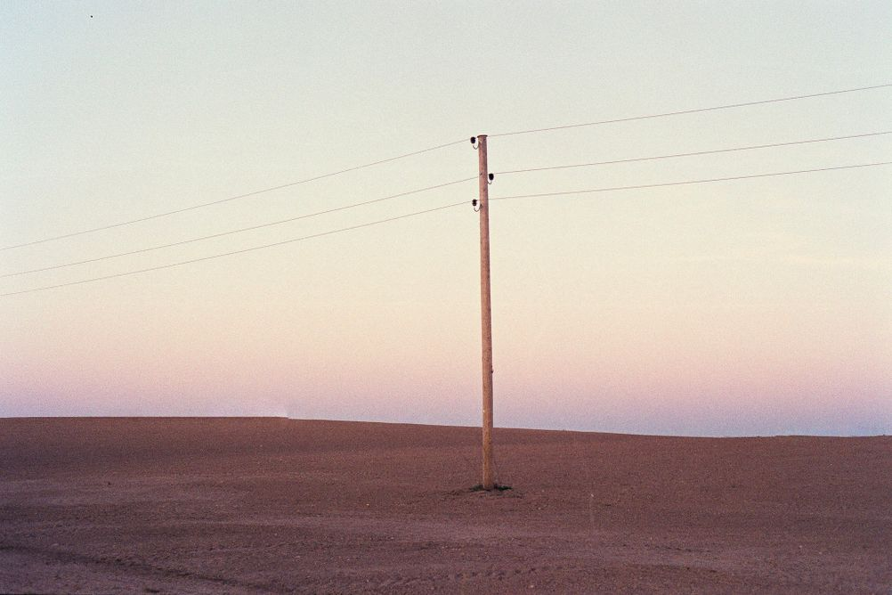 Photo of a single electricity pole in a brown field.