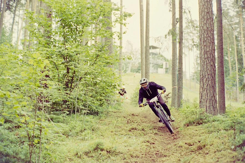 Downhill racer riding fast through a grassy / foresty section