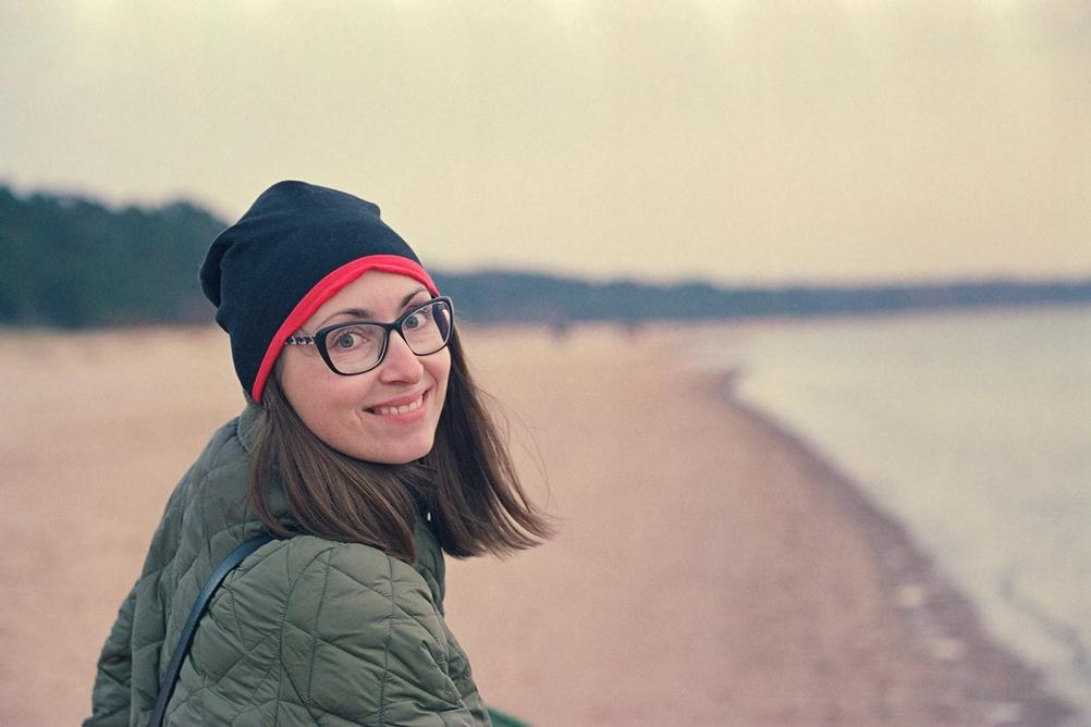 Photo of a smiling woman in beach.