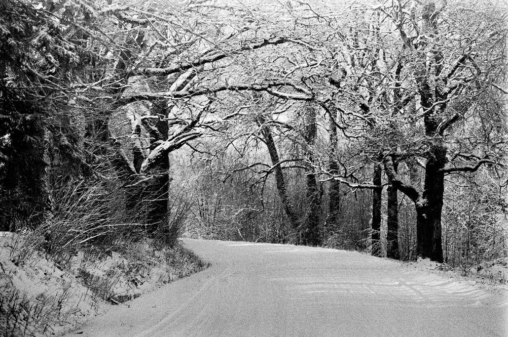 Photo of a road covered in snow with trees around.