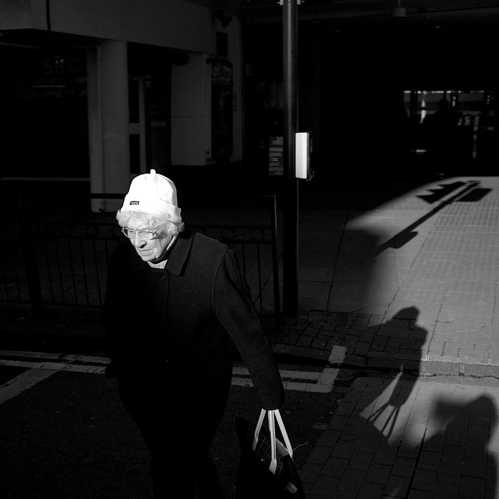 Black and white photo of an old lady walking over street in very harsh light.