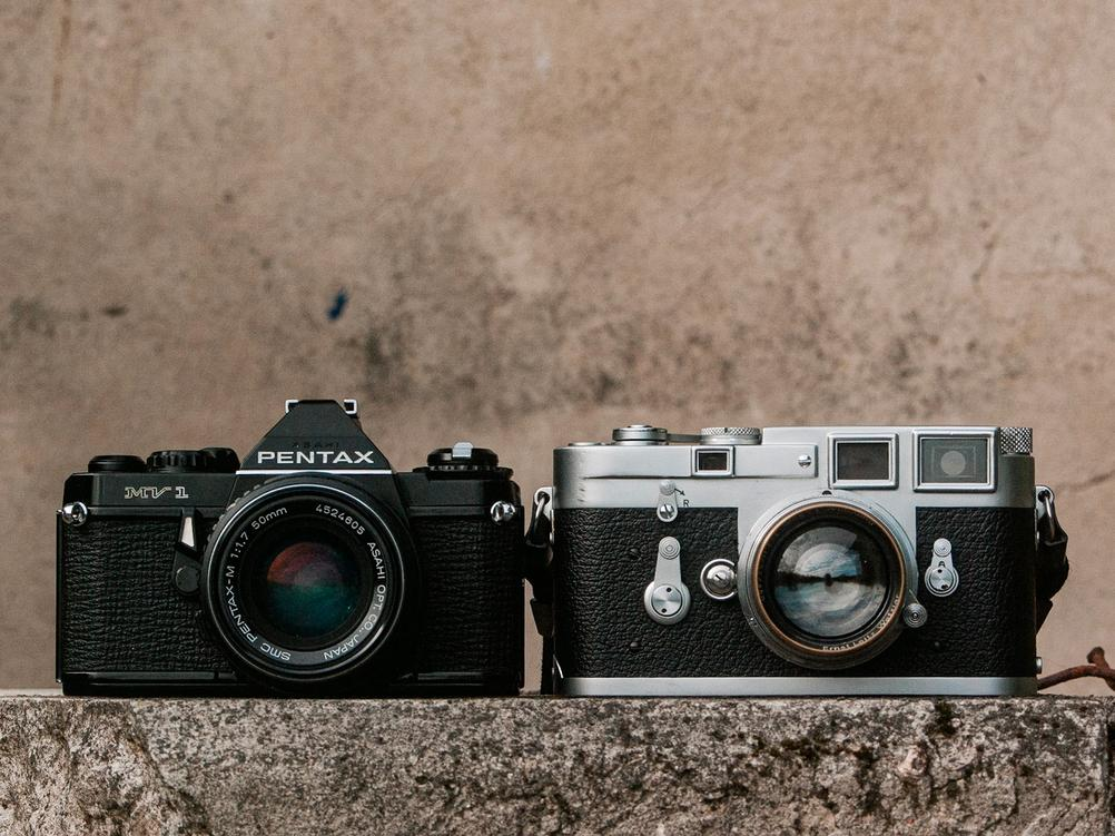 Photo of Pentax MV1 and Leica M3 next to each other.
