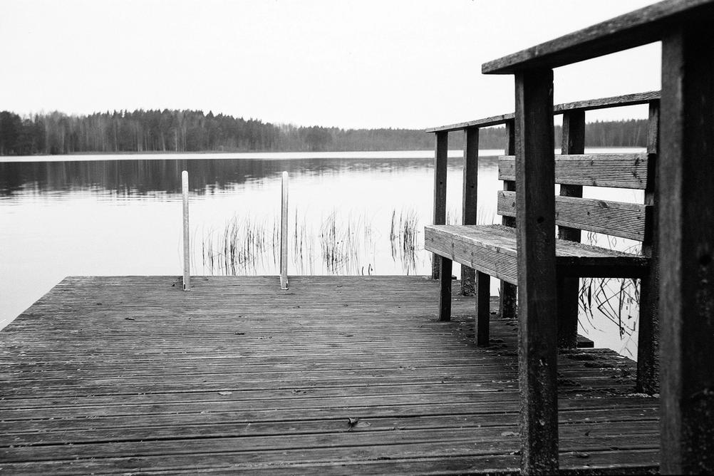 Photo of a bench next to lake.