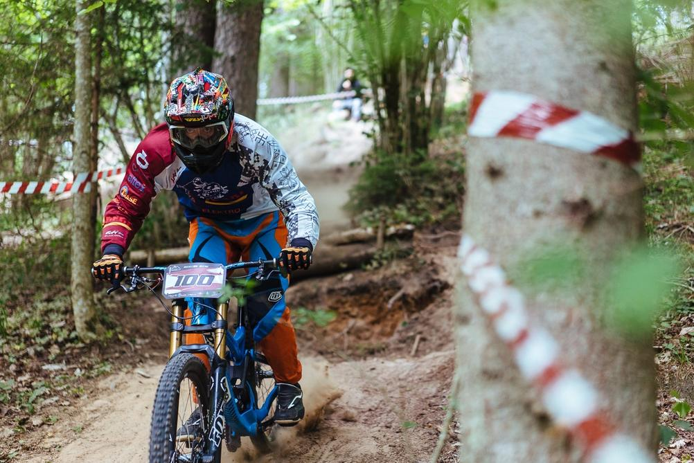 Downhill racer landing from jump with intense focus in eyes during race.