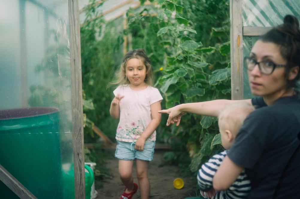 Picture of my wife holding my son and pointing at my daughter whilst they all are next to the greenhouse entrance.