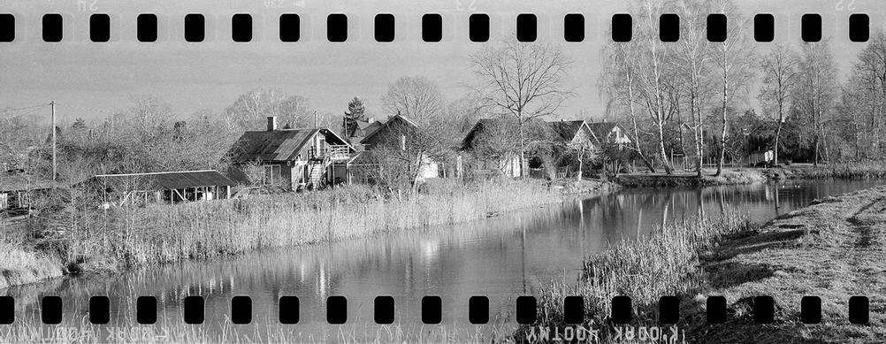 Black and white photo of some houses next to some water.