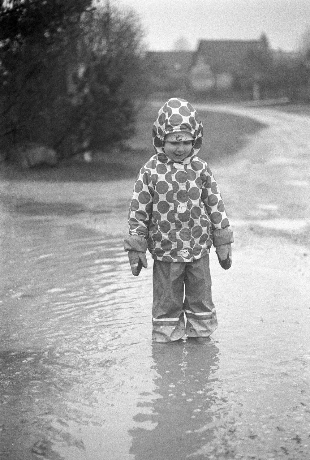 Photo of a young girl in a big puddle.