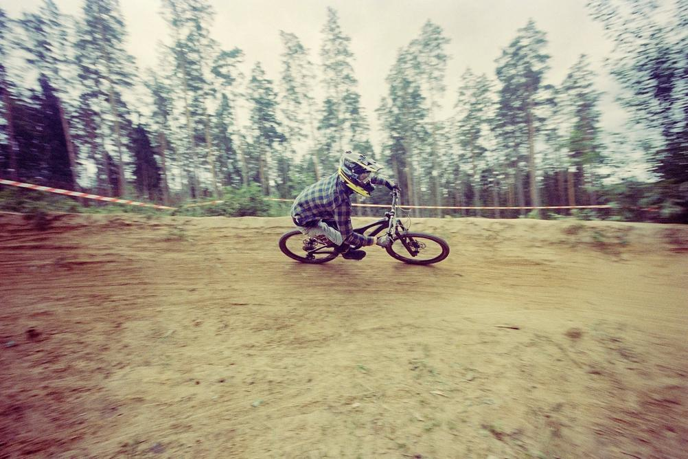 Downhill racer riding berm in high speed.