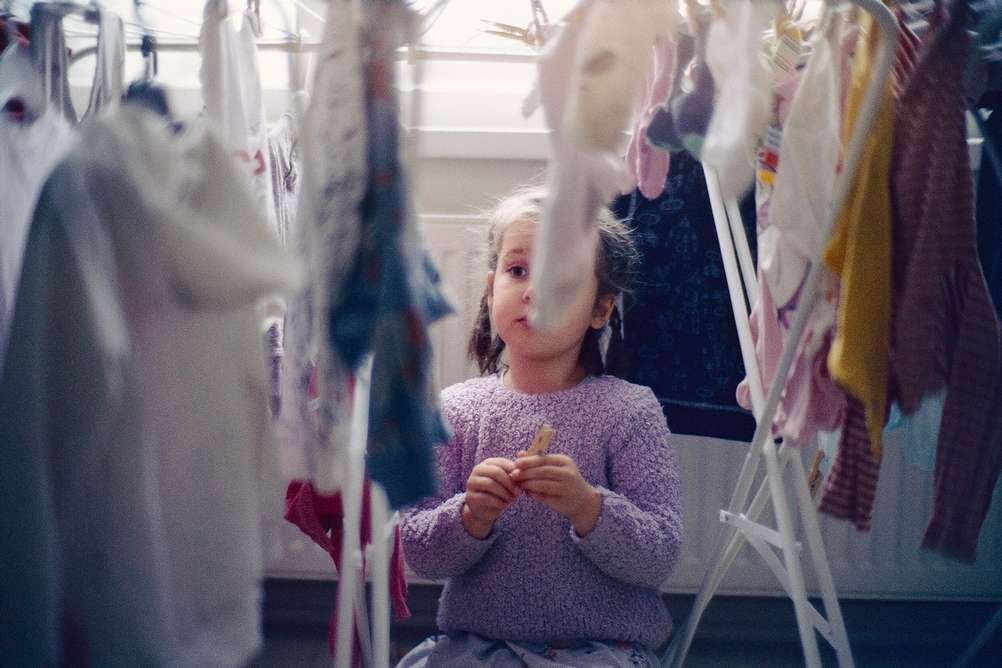 Picture of a 3 year old watching clothes dry.